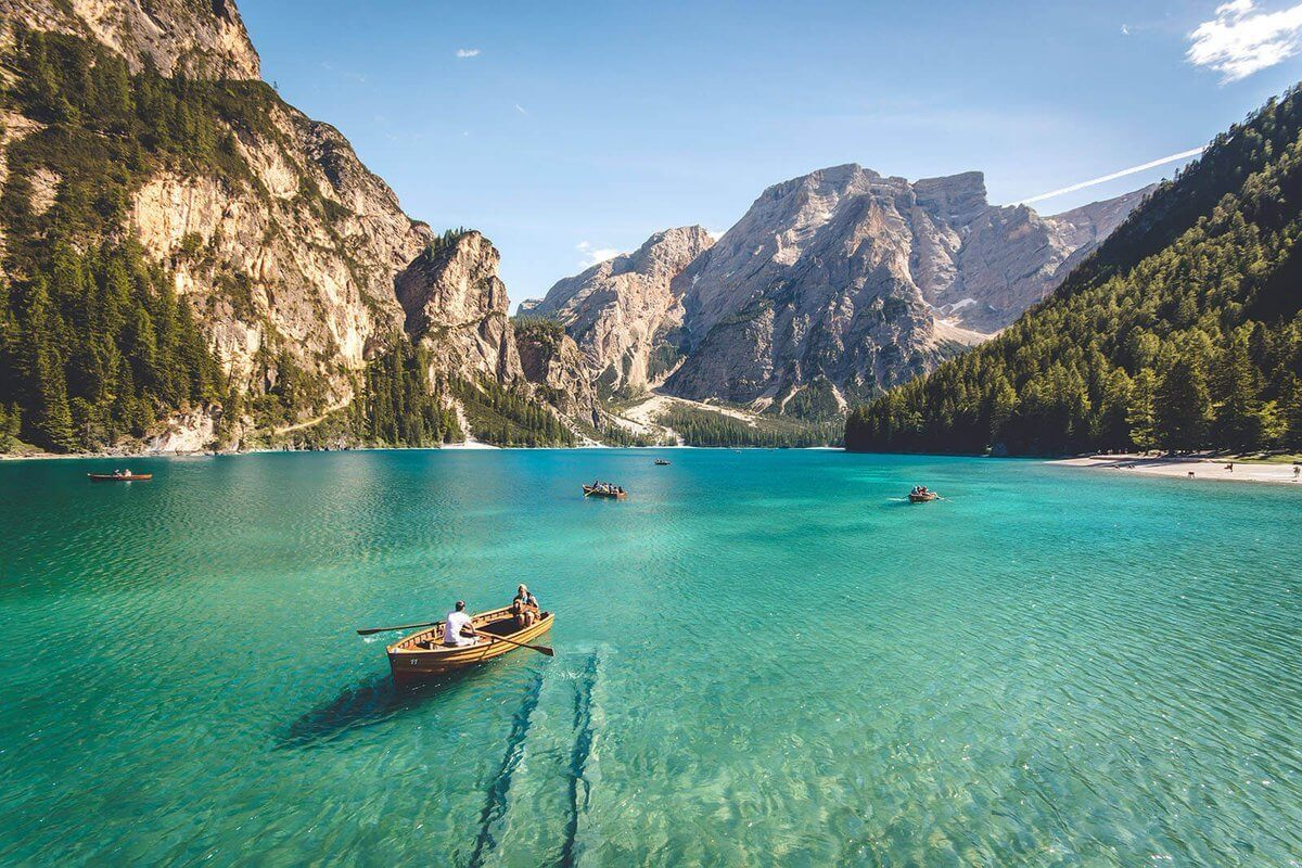three brown wooden boat on blue lake