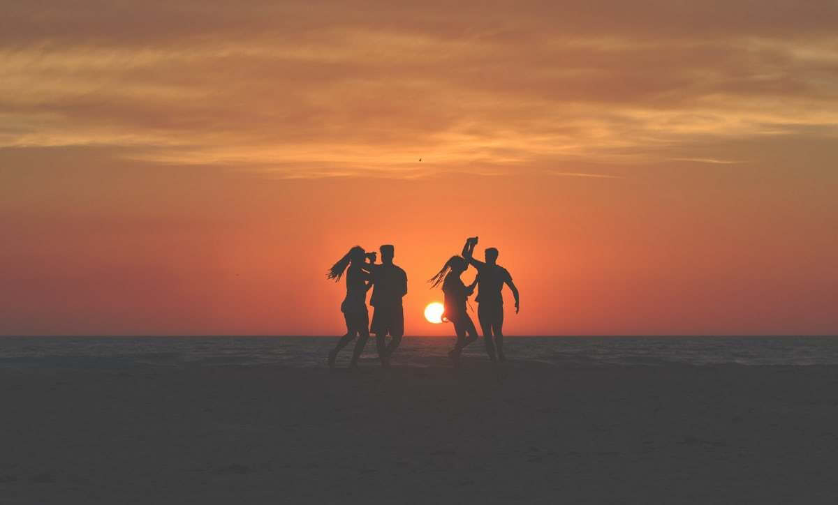 silhouette of four people dancing on beach