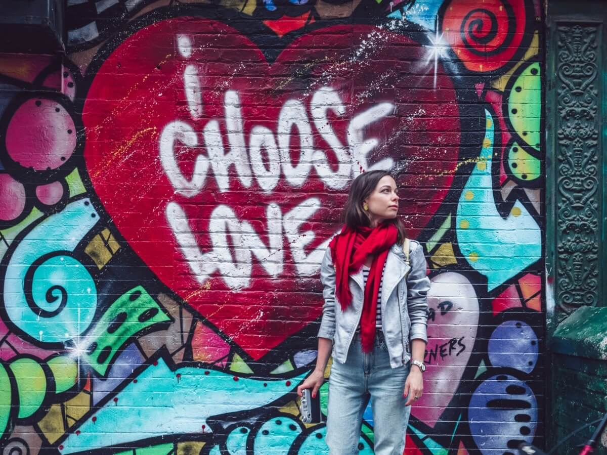 Young woman by the wall with graffiti