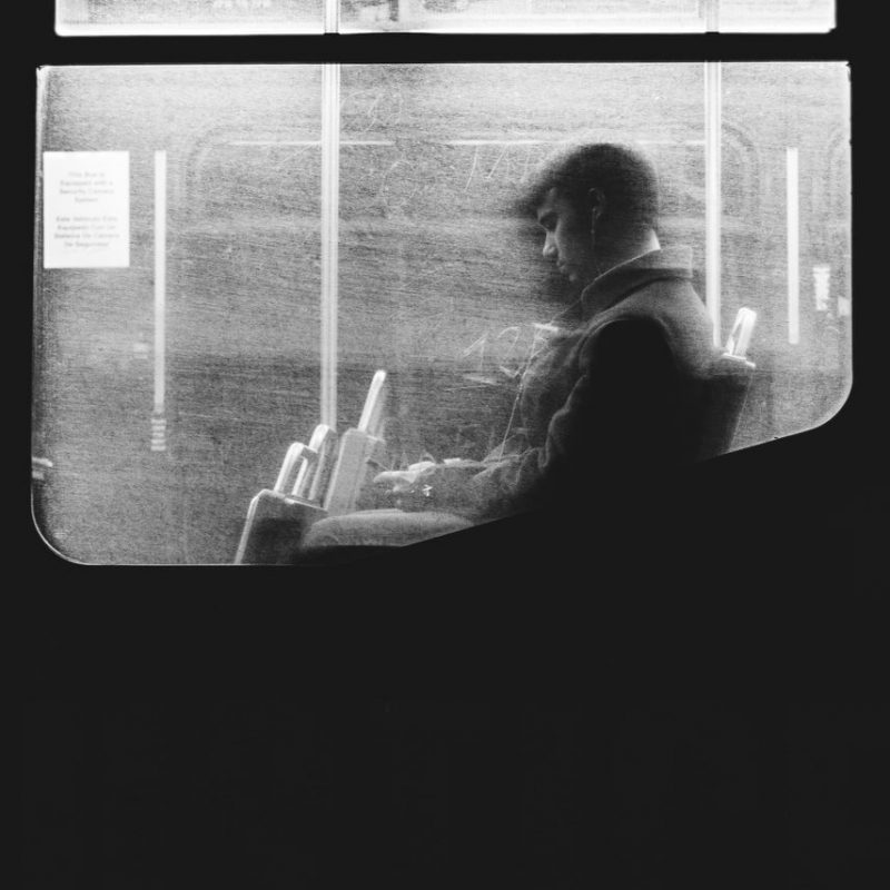 man using phone on the bus