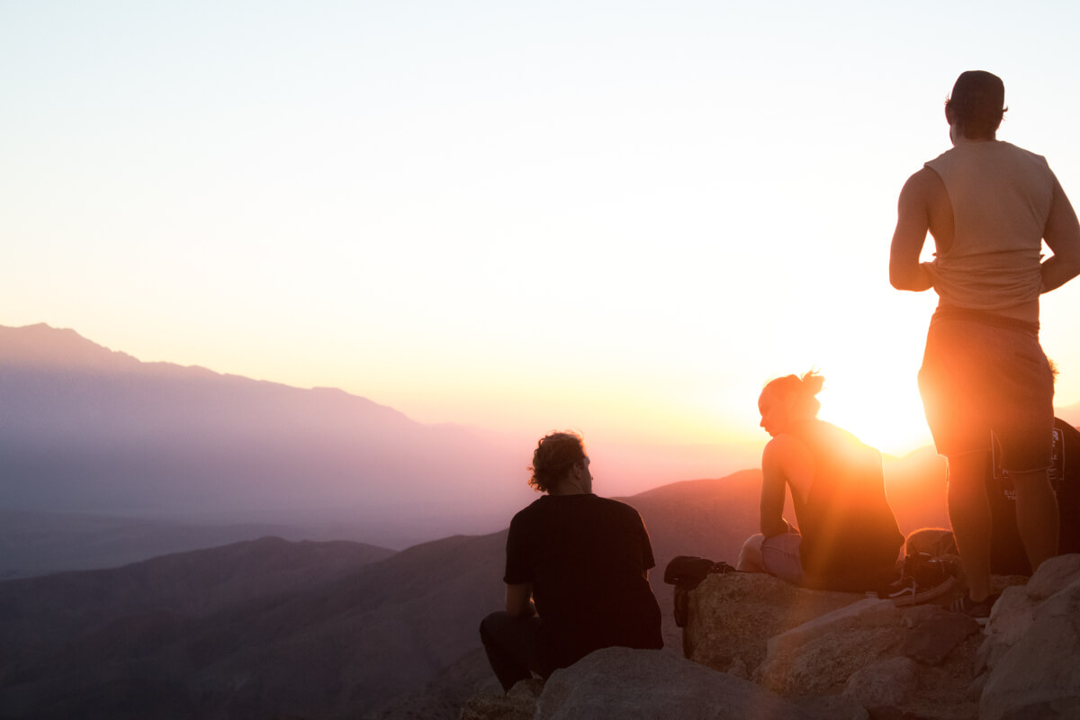 four people near the cliff on golden hour