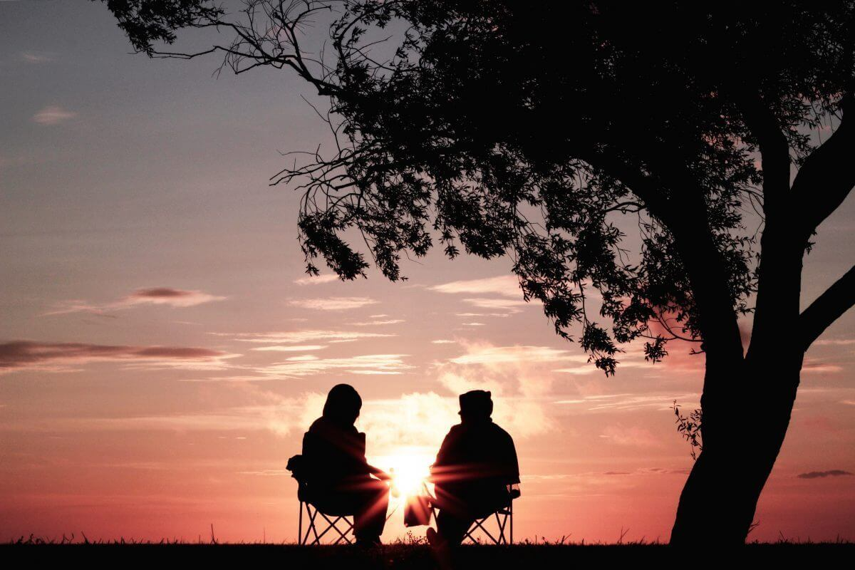 silhouette of two person sitting on chair